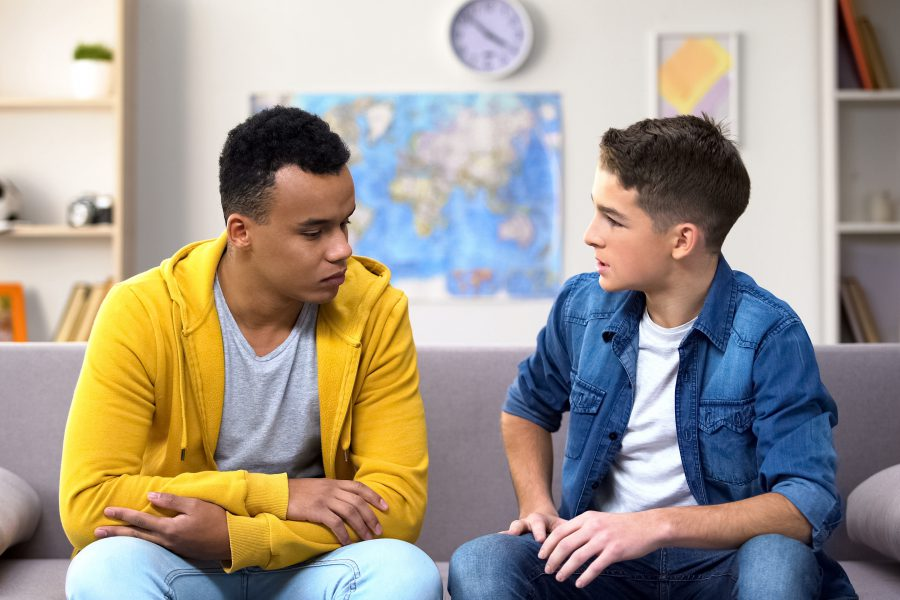 Afro-American teen boy sharing problems with Caucasian friend, bullying problem